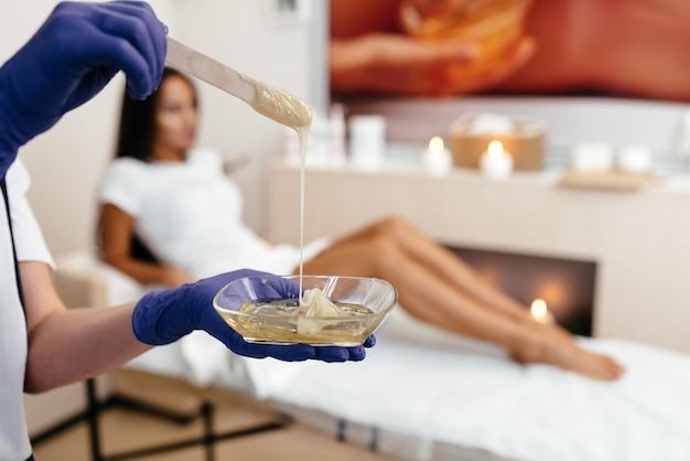 Kosmetikerin, die die beine der jungen frau mit flüssigem zucker im spa-zentrum enthaart. enthaarung der beine mit türkisfarbener shugaring-paste.