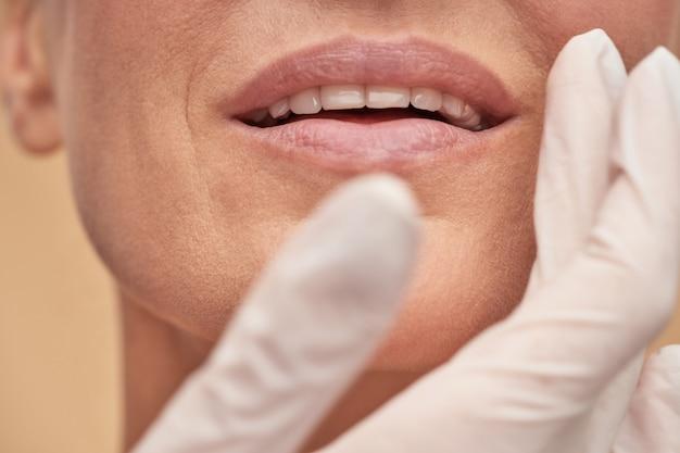 Kosmetikerin, die die weibliche gesichtshaut vor der medizinischen therapie überprüft