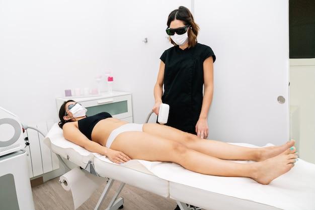 Kosmetikerin, die einer frau am oberschenkel eine laser-haarentfernungsbehandlung gibt und gesichtsmasken trägt, wegen der 2020er covid19-coronavirus-pandemie