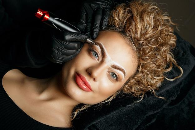 Kosmetikerin, die einer stilvollen jungen frau mit einer weißen brauenpaste augenbrauen-permanent-make-up aufträgt