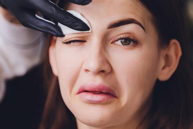 Kosmetikerin, die farbe von der augenbraue des kunden entfernt
