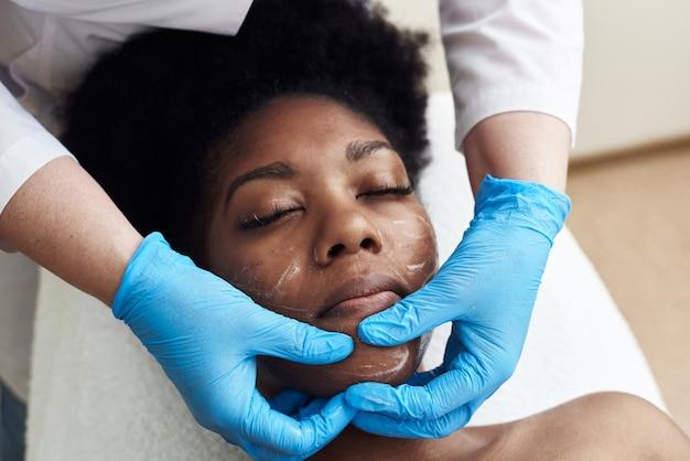 Kosmetikerin, die feuchtigkeitscreme auf einen kunden aufträgt