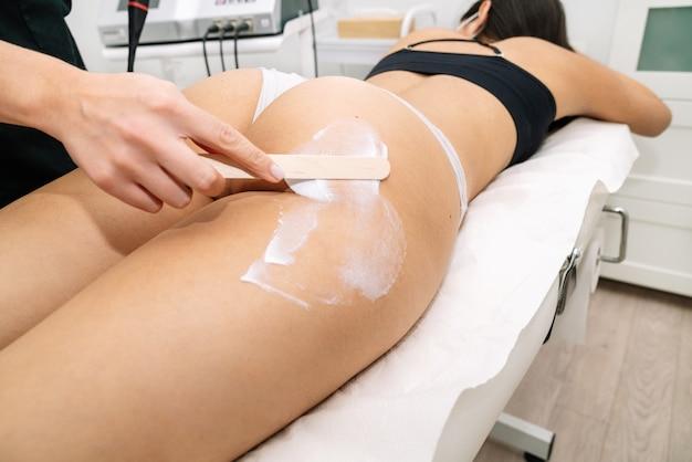Kosmetikerin, die frau am oberschenkel mit epilationswachs behandelt