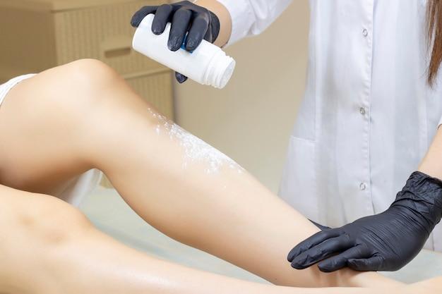 Kosmetikerin, die frauenbeine mit flüssigem zucker im spa-zentrum enthaart