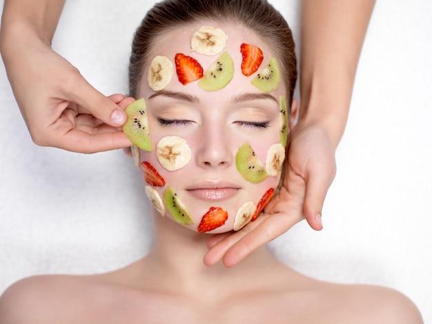 Kosmetikerin, die fruchtmaske auf einem gesicht der schönen jungen frau tut - drinnen