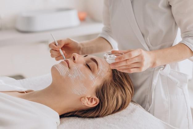Kosmetikerin, die gesichtsbehandlung macht und gesichtsmaske anwendet