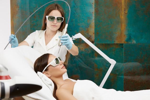 Kosmetikerin, die gesichtsbehandlung mit laser für fantastische frau tut, die im weißen bett am spa-salon liegt