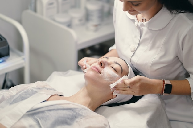 Kosmetikerin, die gesichtsbehandlung zu einer schönen frau macht