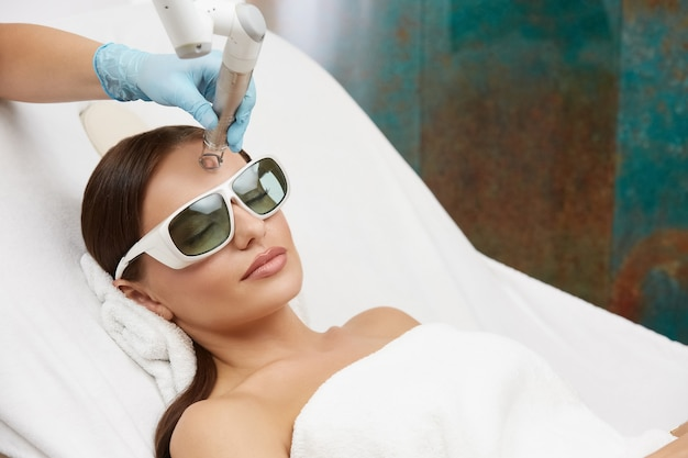Kosmetikerin, die gesichtsprozeduren in der kosmetikklinik unter verwendung des lasers tut, frau, die gesichtsbehandlung auf ihrer stirn erhält