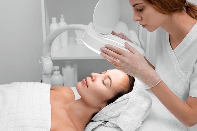 Kosmetikerin, die gesichtsschönheitsroutine für kundin tut