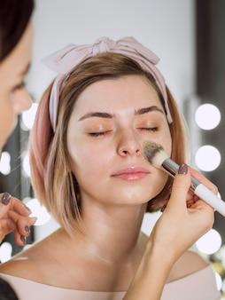 Kosmetikerin, die grundierung auf frau anwendet
