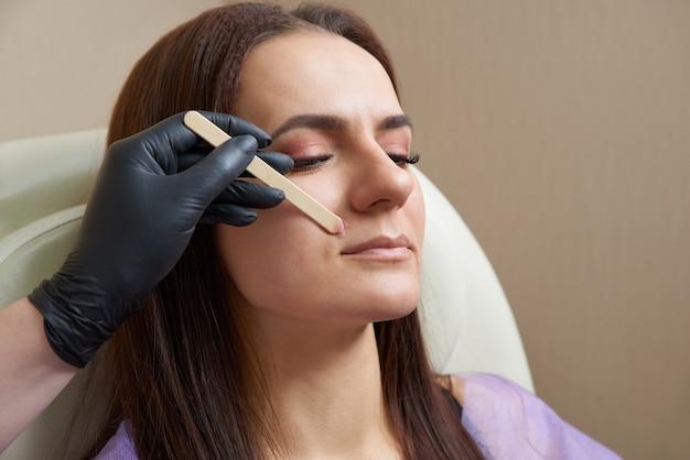 Kosmetikerin, die haare über oberlippe der jungen frau im salon entfernt. schnurrbart-enthaarung
