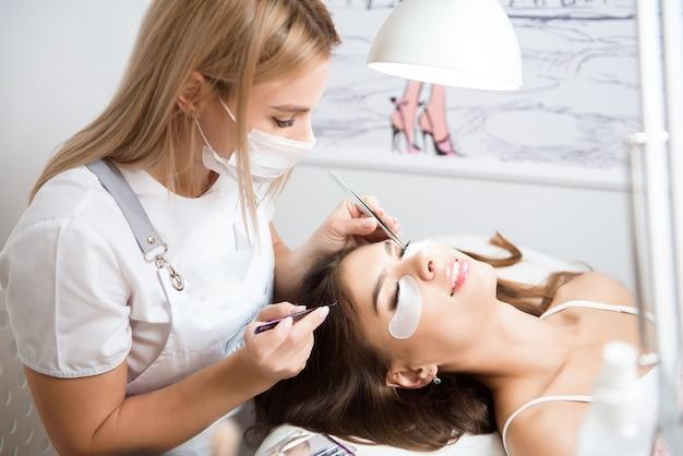 Kosmetikerin, die in einem schönheitsstudio an der aufwertung von seidenwimpern arbeitet.