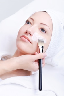 Kosmetikerin, die kosmetische maske im spa-salon für junge frau anwendet