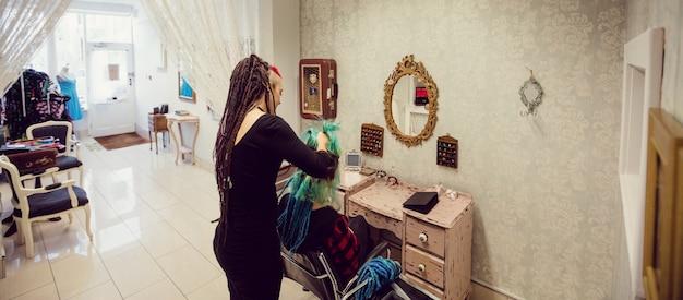 Kosmetikerin, die kundenhaare stylt