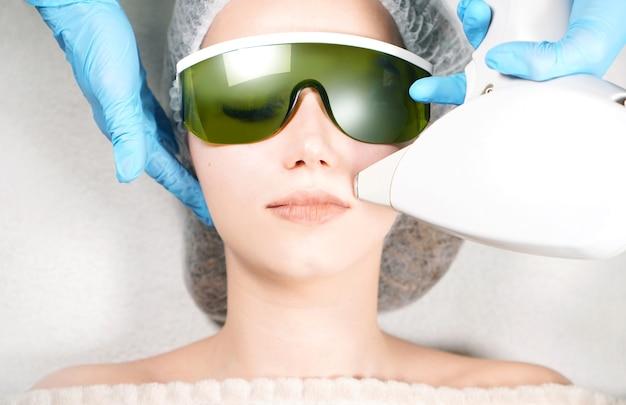 Kosmetikerin, die laser-haarentfernung auf gesicht der jungen frau tut