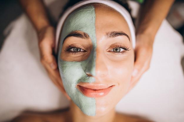 Kosmetikerin, die maske auf einem gesicht des kunden in einem schönheitssalon anwendet