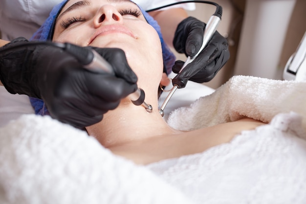 Kosmetikerin, die mikrostromverfahren am klienten durchführt