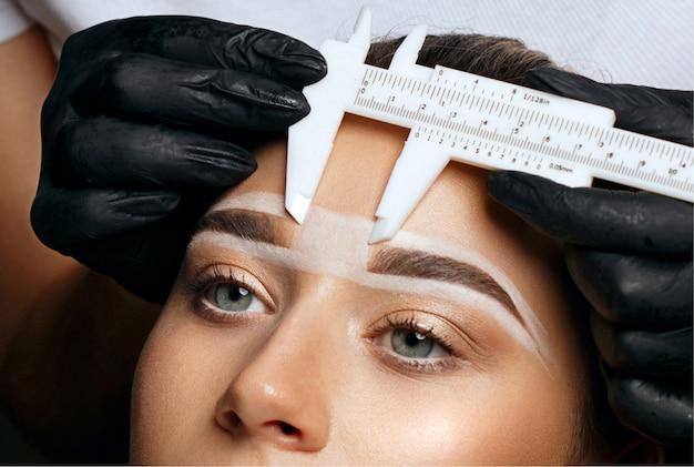 Kosmetikerin, die mit messschiebern vor dem permanenten augenbrauen-make-up maß nimmt