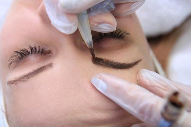 Kosmetikerin, die permanent make-up auf augenbrauen-augenbrauentattoo aufträgt
