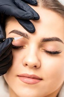 Kosmetikerin, die permanentes make-up auf augenbrauen der jungen frau anwendet