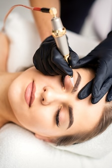 Kosmetikerin, die permanentes make-up auf augenbrauen der jungen frau durch spezielle tätowiermaschine aufbringt