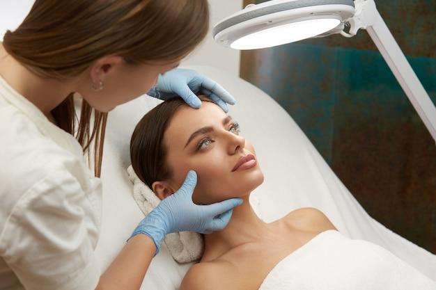 Kosmetikerin, die schönes frauengesicht in den blauen handschuhen in der kosmetikklinik berührt
