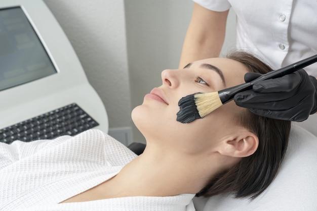 Kosmetikerin, die schwarze maske auf dem gesicht einer schönen reifen frau für kohlenstoffschälen anwendet