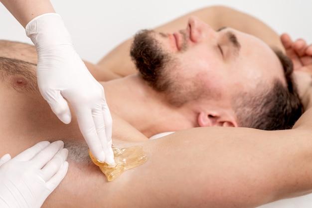 Kosmetikerin, die wachspaste auf männliche achselhöhle aufträgt