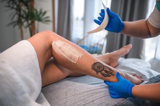 Kosmetikerin, die weibliche beine im schönheitssalon-kosmetikkonzept des spa-centers einwachst