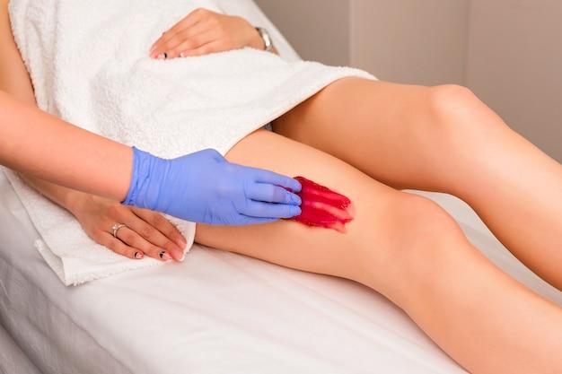 Kosmetikerin, die weibliche beine im spa-zentrum wächst. entfernen sie unnötige haare an den beinen.
