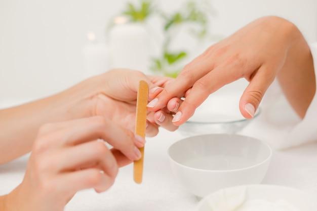 Kosmetikerin, die weibliche kundennägel am badekurortschönheitssalon archiviert