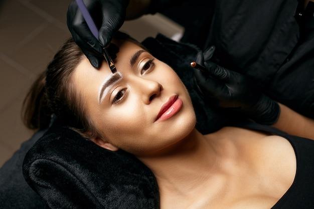 Kosmetikerin, die weißen bleistift aufträgt und mit einem pinsel mischt. vorbereitung auf ein pudersputterndes permanent-brauen-make-up