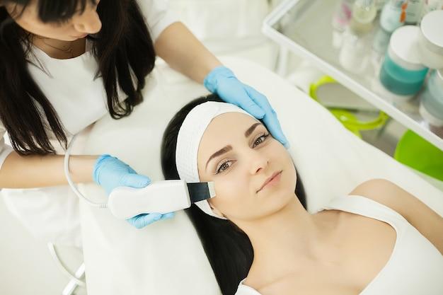 Kosmetikerin, die weißes kosmetisches pulver aufträgt