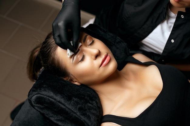 Kosmetikerin entfernt weiße brauenpaste nach der modellierung der brauenform