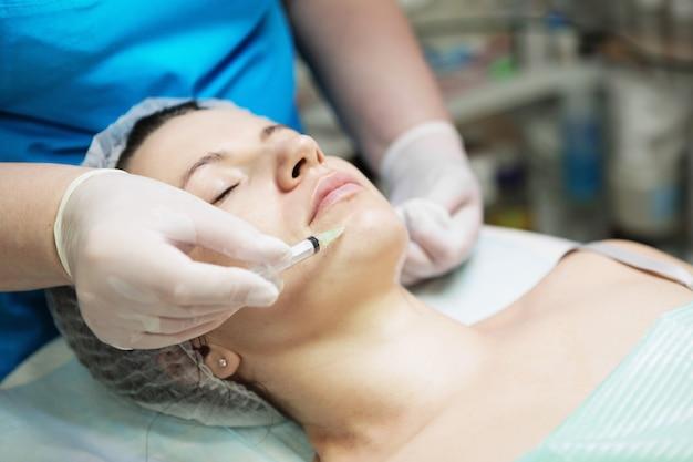 Kosmetikerin führt eine nadel-mesotherapie-behandlung im gesicht einer frau durch