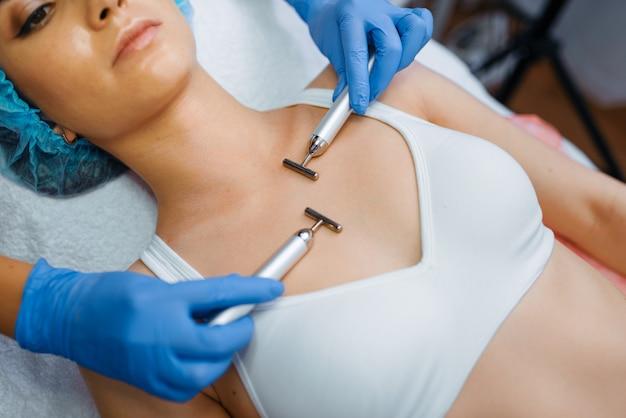 Kosmetikerin glättet die körperhaut nach botox-injektionen. verjüngungsverfahren im kosmetiksalon. arzt und frau, schönheitschirurgie gegen falten und alterung
