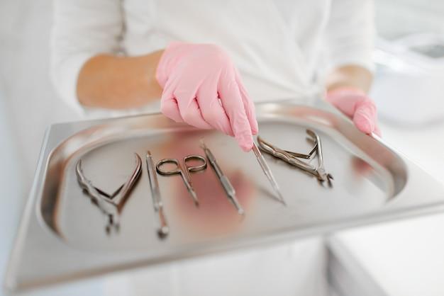 Kosmetikerin hält metallschale mit ausrüstung