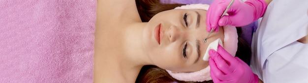 Kosmetikerin im spa-schönheitssalon, die aknebehandlung mit mechanischem instrument durchführt. konzept der medizinischen behandlung von verjüngung und hautpflege