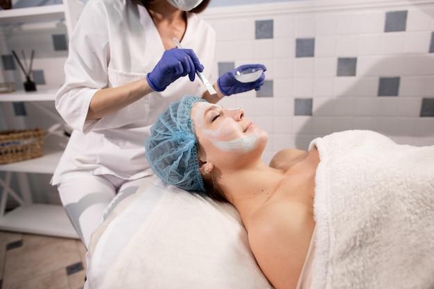 Kosmetikerin in blauen handschuhen, mit einem pinsel eine maske auf das gesicht des patienten auftragen
