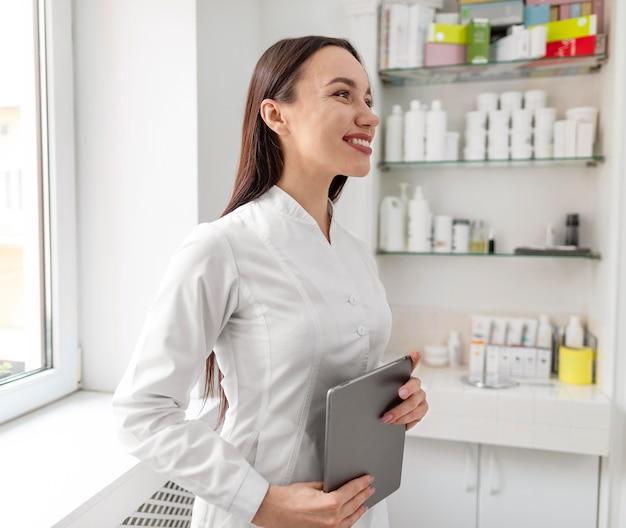 Kosmetikerin in der klinik mit tablette