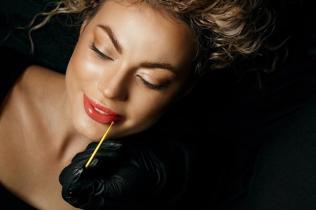 Kosmetikerin in handschuhen, die einer entzückenden frau während des lippen-permanent-make-up-verfahrens lippenbehandlungsbalsam aufträgt. nahaufnahme