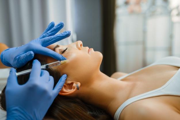 Kosmetikerin in handschuhen gibt der patientin auf dem behandlungstisch botox-injektionen im gesicht. verjüngungsverfahren im kosmetiksalon. arzt und frau, schönheitschirurgie gegen falten