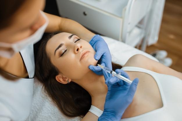 Kosmetikerin in handschuhen gibt der patientin auf dem behandlungstisch eine kinn-botox-injektion. verjüngungsverfahren im kosmetiksalon. arzt mit spritze und frau, schönheitschirurgie gegen falten