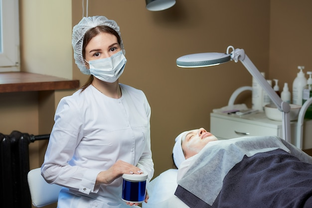 Kosmetikerin in maske posiert mit hautpflegeprodukt in der nähe des patienten