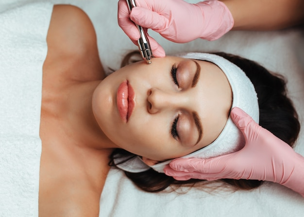 Kosmetikerin in rosa handschuhen, die mikrodermabrasion tun
