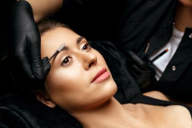 Kosmetikerin kämmt augenbrauen mit einer bürste vor dem brauen-tattoo-verfahren. nahaufnahme eines models mit einem schönen gesicht