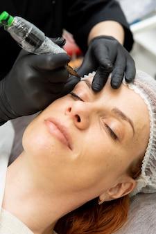 Kosmetikerin macht dauerhafte make-up augenbrauen
