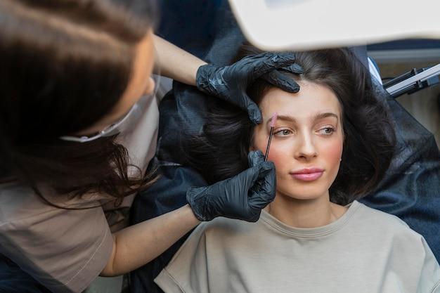 Kosmetikerin macht eine augenbrauenbehandlung für ihren klienten
