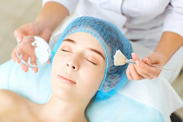 Kosmetikerin macht einer jungen frau in einem schönheitssalon schönheitsmaske.